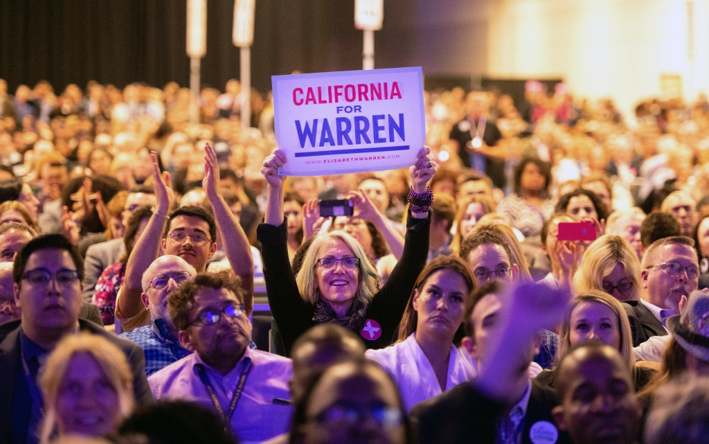 A woman holds up a sign showing support for Democratic presidential candidate for Elizabeth Warren as she speaks on stage during the 2019 California Democratic Party State Convention