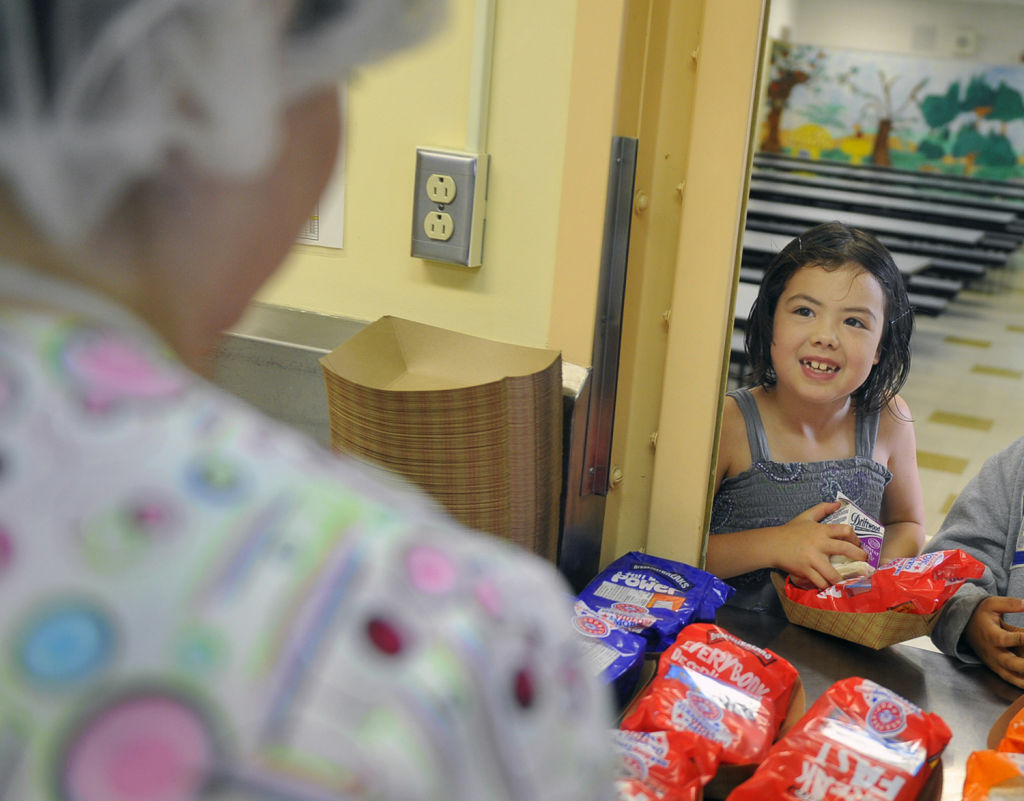 A student talks with cafeteria worker Sophia Villareal as she picks up her breakfast at Brockton Elementary School.
