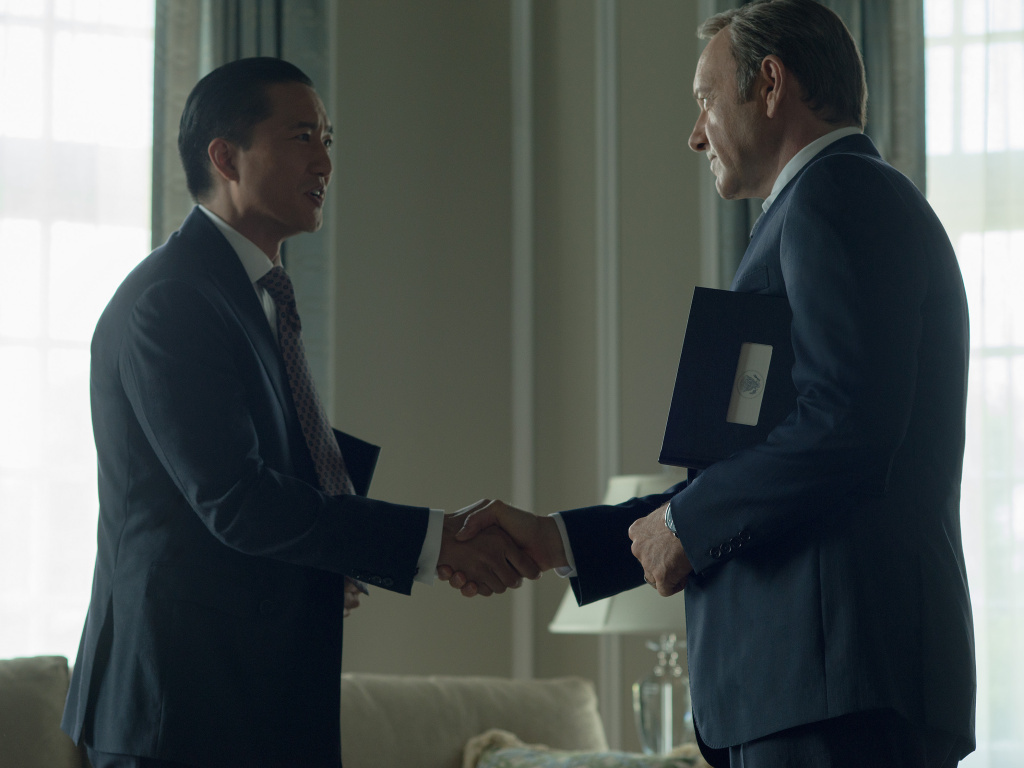Chinese billionaire Xander Feng, played by Terry Chen, shakes hands with Francis Underwood, played by Kevin Spacey, in Netflix's