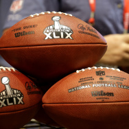 An employee of the Wilson Sporting Goods Co. puts the finishing touches on a replica Super Bowl XLIX football at the NFL Experience Saturday, Jan. 24, 2015, in Phoenix. The company set up a production line to manufacture the footballs which are sold to the public at the event. (AP Photo/Charlie Riedel)