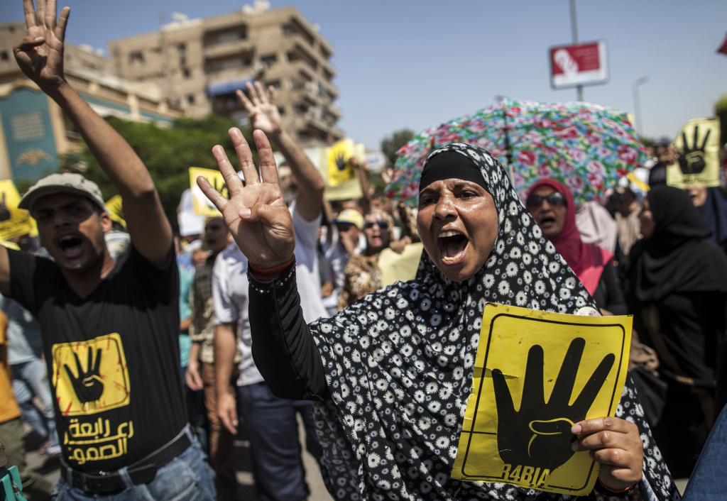 Supporters of ousted Egyptian president Mohamed Morsi raise up posters with the four finger symbol during a demonstration against the military backed government in the Egyptian capital Cairo, on September 13, 2013. An Egyptian court Monday banned all Muslim Brotherhood activity and seized the group's financial assets.