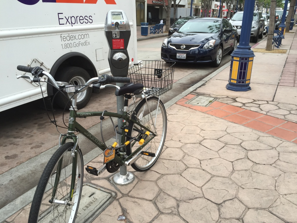 A bike is locked to a parking meter illegally in Westwood Village. But a new city plan to install hitches on meters could make this kind of bike parking legal.