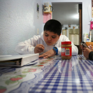 (Lt. to Rt.) Edwin Bernal, 9, finished homework, while his brother Angel Lozano, 5, watches videos before school at their home in Los Angeles, Friday January 20, 2017. Last year Edwin was among a group of undocumented children, who qualified for Medi-Cal coverage through a state funded program. His brother is covered because he was born in the United States. His mother fears that under the Trump administration the program will be in danger and he will no longer have medical coverage. (Photo By Maria J. Avila/CalMatters)