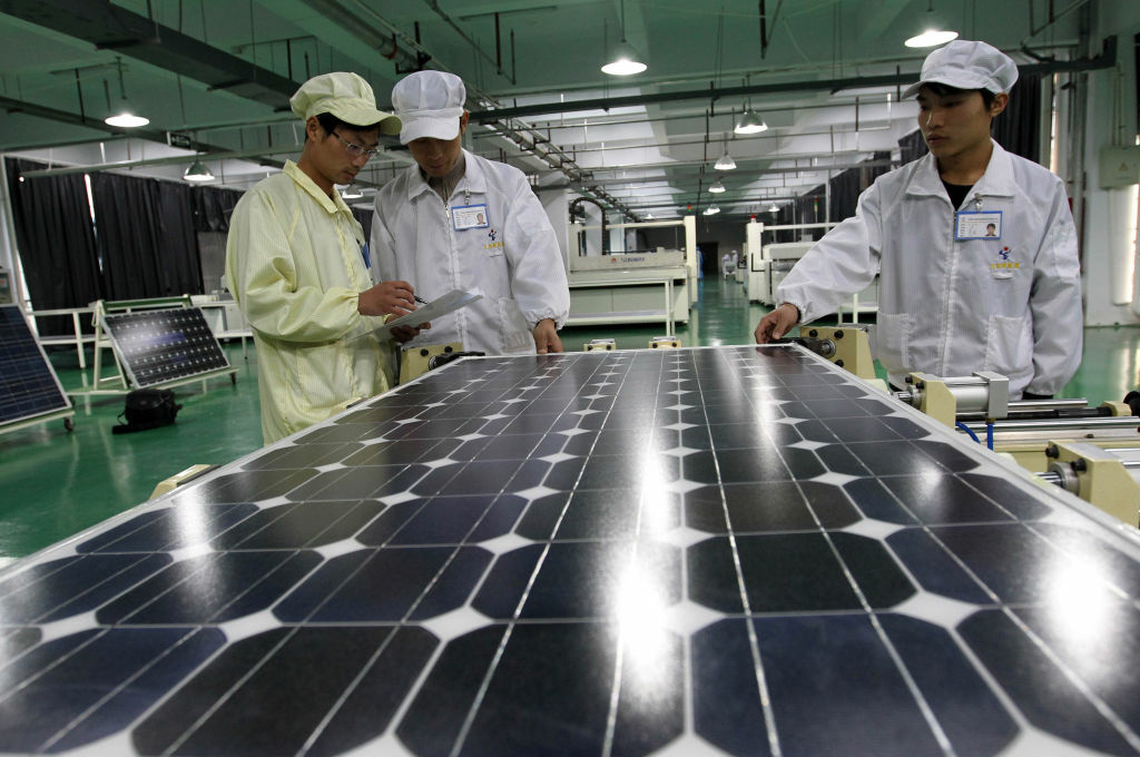 Chinese workers inspect a solar panel at the Tianxiang Solar Energy Equipment Factory in Huaibei, east China's Anhui province on March 21, 2012.  China sought to defuse a trade row with the US after the latter imposed duties on Chinese solar products, saying it would not hurt ties, even as state media cried protectionism.