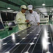 Chinese workers inspect a solar panel at