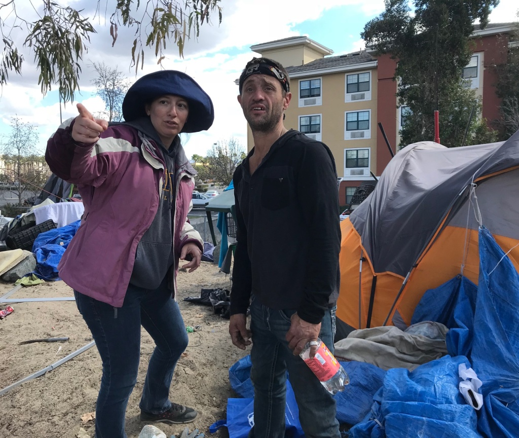 Brooke Weitzman, a lawyer for the homeless, urges a riverbed resident to pack up so he can go spend the night at a motel on Feb. 21, 2018. County officials are now nearing a deadline to transition people out of the motels into more permanent housing.