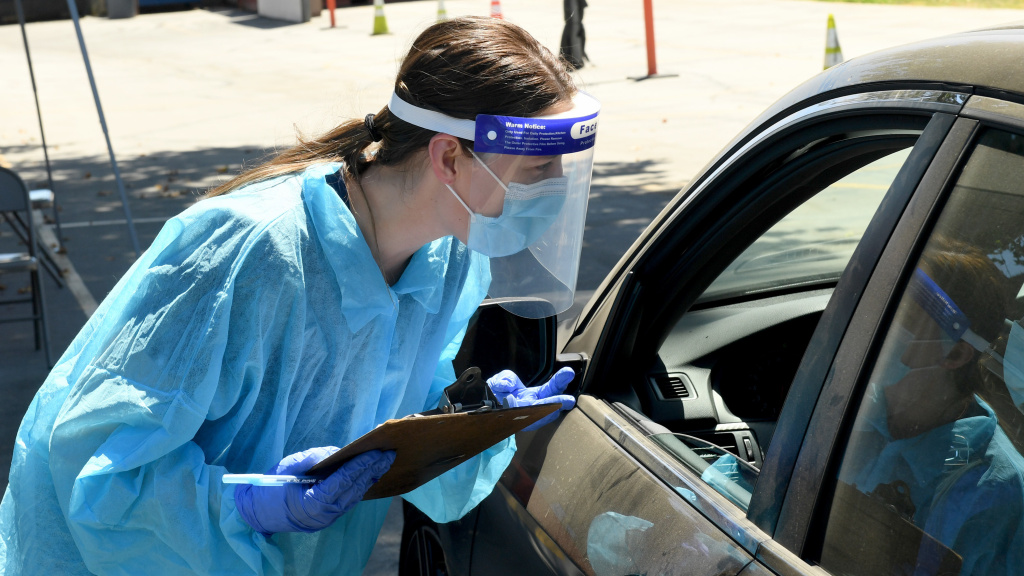 An urgent care worker wears personal protective equipment to perform drive-up COVID-19 testing in Winnetka, Calif. Leading public health scientists tell journalist Alexis Madrigal that widespread at-home testing could help contain the virus.