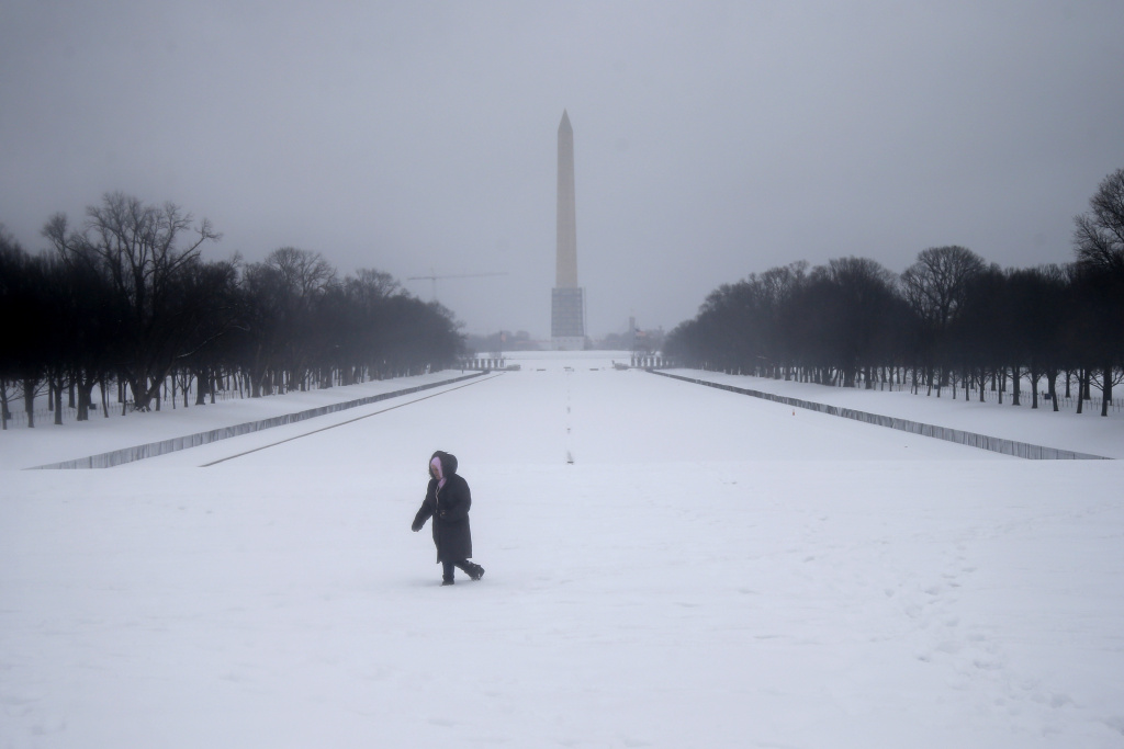 Maria Valero walks in the snow after taking photographs of the reflecting pool and the Washington Monument in Washington on Thursday.