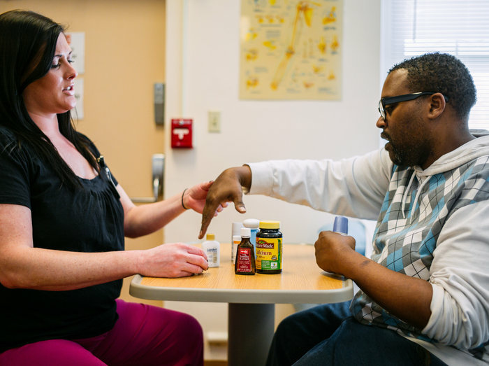 Occupational therapist Lydia Bongiorni works with Troy Hodge on grasping and lifting objects at a rehabilitation center in Gwynn Oak, Md.