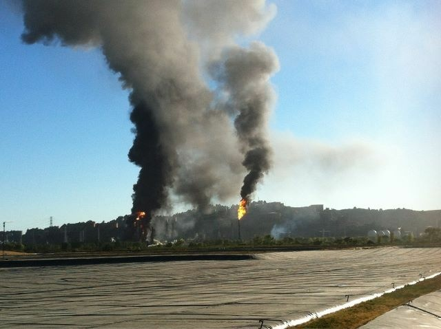 Black plumes of smoke erupt from a fire that is currently burning at a Chevron refinery near Richmond, CA.