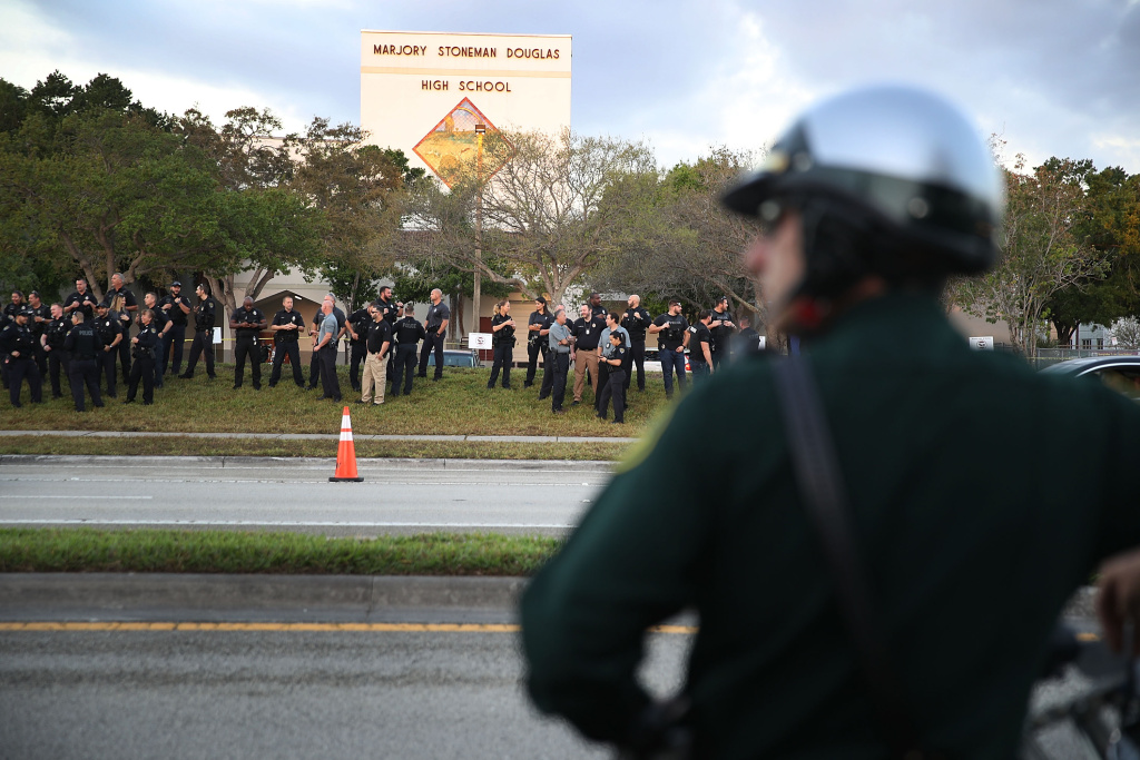 Police officers stand in front of Marjory Stoneman Douglas High School as student arrive to attend classes for the first time since the shooting that killed 17 people on February 14  at the school on February 28, 2018 in Parkland, Florida. Police arrested 19-year-old former student Nikolas Cruz for the 17 murders.