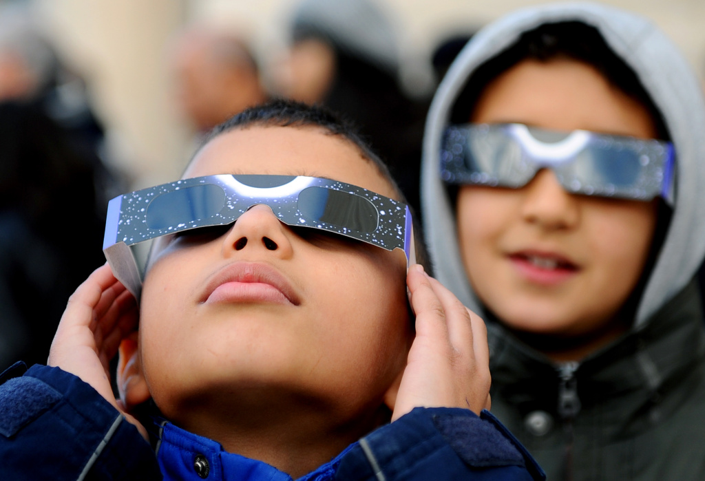 Children wear special glasses as they watch the first partial solar eclipse of 2011 on January 4, 2011 in Tunis. A solar eclipse happens when the Moon swings between the Earth and the Sun.