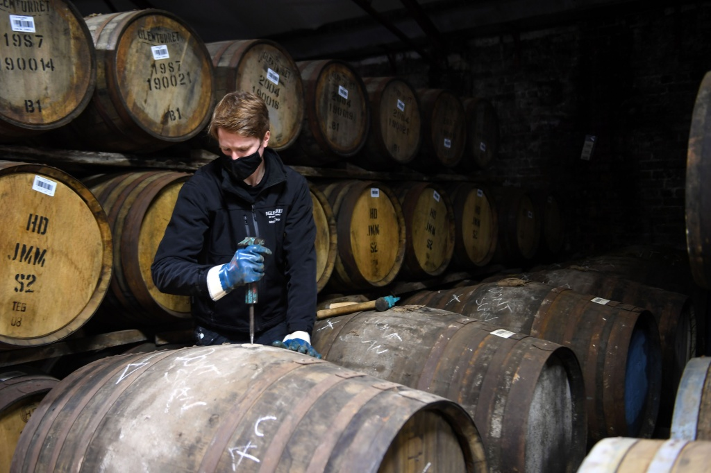 Employee Matthew Coulson poses for a photograph with whisky casks in the bonded warehouse at The Glenturret Distillery in Crieff, central Scotland, on February 26, 2021.
