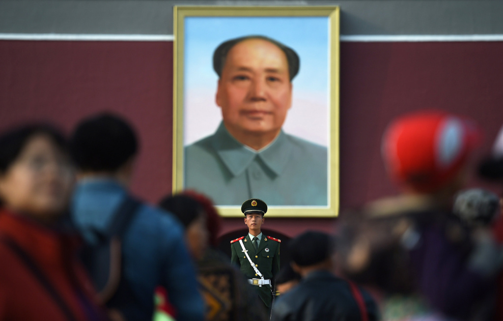 Visitors walk past a portrait of late communist leader Mao Zedong on Tiananmen Gate in Beijing on Sept. 30, the eve of National Day.
