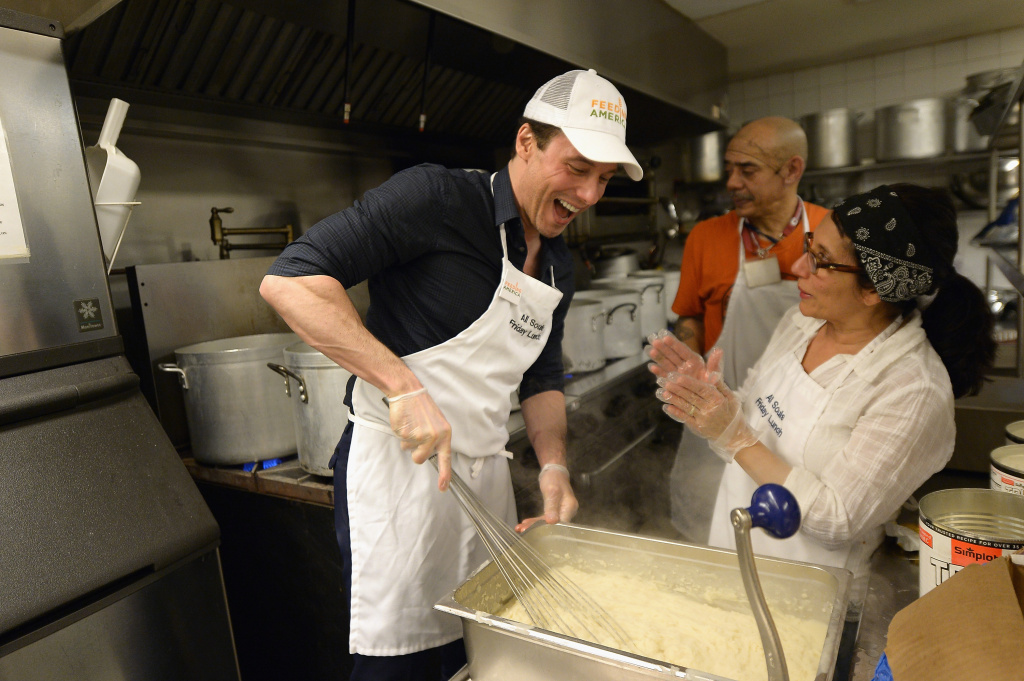 Rocco DiSpirito and Karolina Kurkova attands the Feeding America's Pledge To Volunteer Event At All Souls Friday Soup Kitchen on February 12, 2016 in New York City.