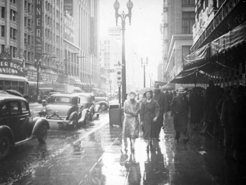 This view looking north on Hill from Seventh Street captures cars driving and people walking in the rain. The movie