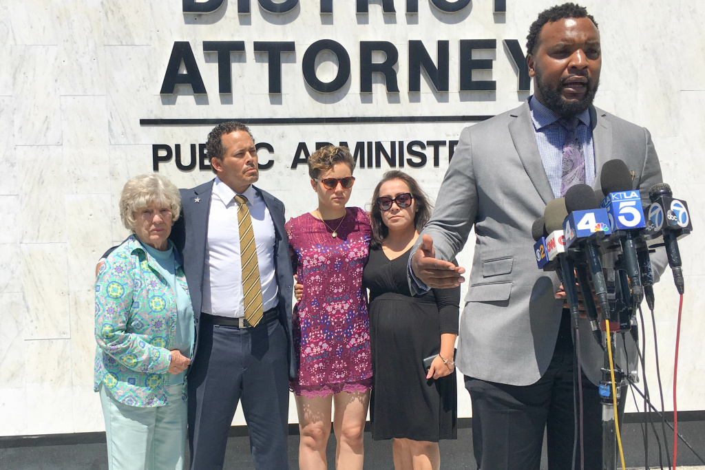The family of Hannah Williams (from left to right, her grandmother Lynn Younger Williams, her father Benson Williams, her older sister Nyla Williams, and her mother Pilar Looney) and their attorney, S. Lee Merritt (foreground), hold a press conference outside the Orange County District Attorney's office in Santa Ana on July 12, 2019.