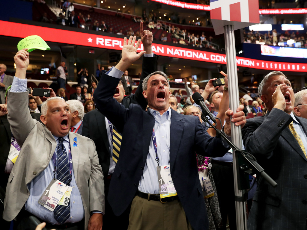 Former Virginia Attorney General Ken Cuccinelli (left) along with other delegates from Virginia chants for a roll call vote on Monday, the first day of the Republican National Convention, at the Quicken Loans Arena in Cleveland.
