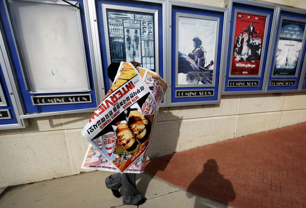 A worker carries a poster for the movie <em>The Interview</em> away from its display case at a theater in Atlanta.
