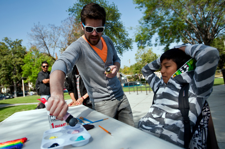 Art Center teacher and graduate Patrick Hruby works with Washington Accelerated Elementary fourth grader Tandy Ellis paint the words,