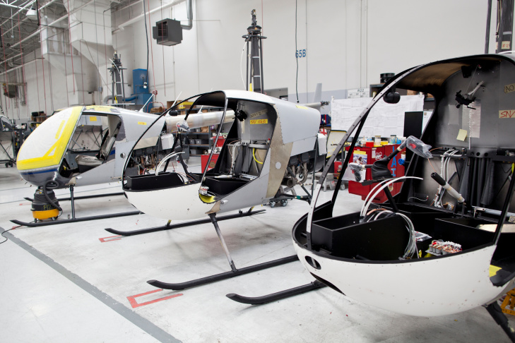 Jonathan Mora, an avionics mechanic, works underneath a Raven II helicopter on Friday, Nov. 1 at Robinson Helicopter Co. in Torrance. The family-owned business is is the largest manufacturer of civilian helicopters in the world.
