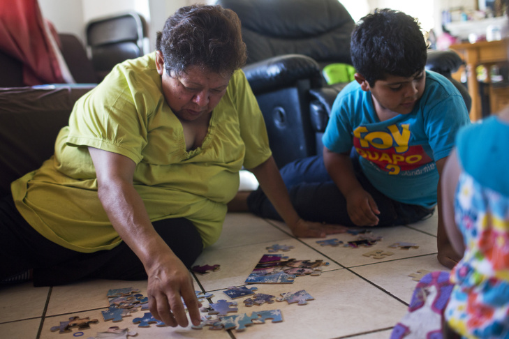Three-year-old Soledad Garcia lies on her grandmother's back as they put a