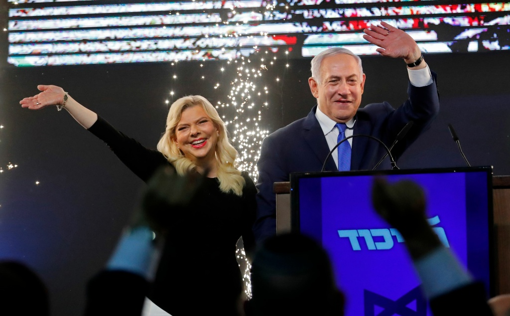 Israeli Prime Minister Benjamin Netanyahu, accompanied by his wife Sara, greets supporters on election night at his Likud Party headquarters in the Israeli coastal city of Tel Aviv early on April 10, 2019.