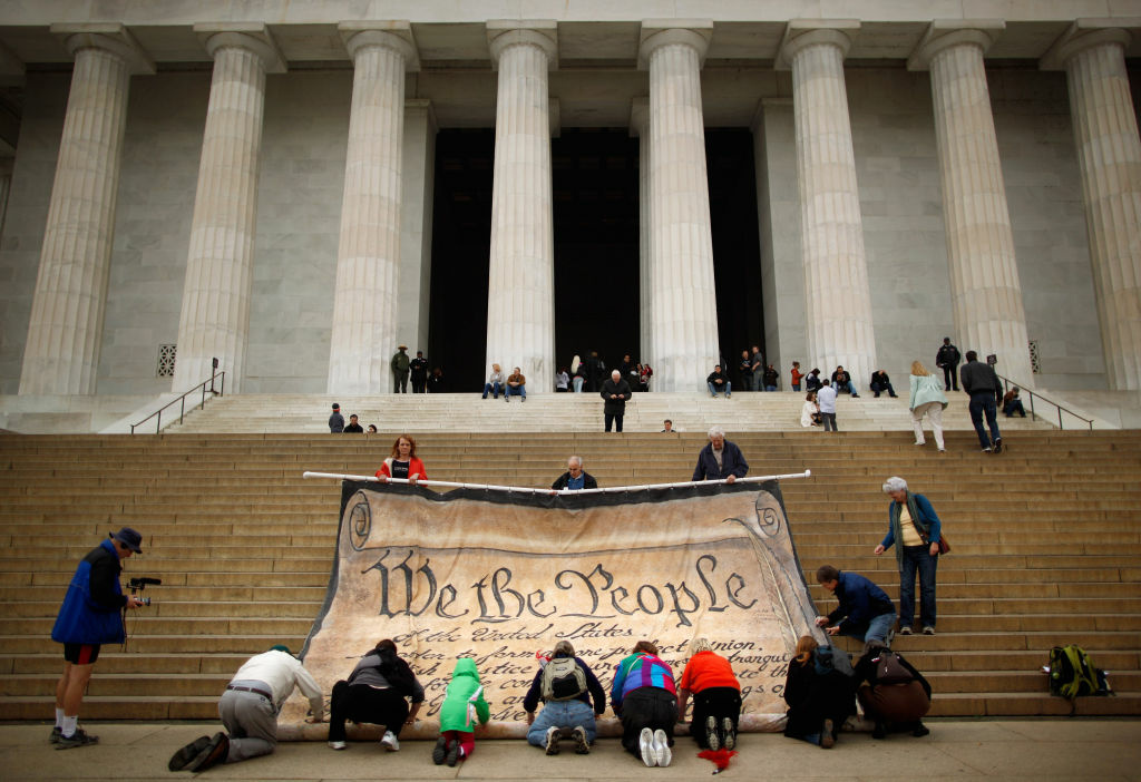 Volunteers help roll up a giant banner printed with the Preamble to the United States Constitution during a demonstration against the Supreme Court's Citizens United ruling at the Lincoln Memorial on October 20, 2010.