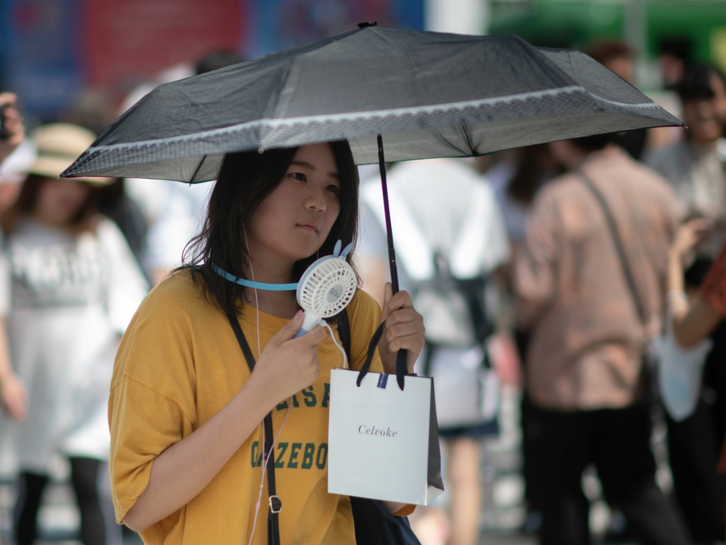 A woman uses a portable fan to cool herself in Tokyo on Tuesday as Japan suffers from a heat wave. Scientists say extreme weather events will likely happen more often as the planet gets warmer.