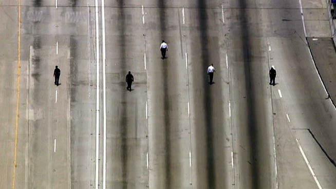 Investigators walked a portion of the 110 Freeway in South Los Angeles on Tuesday in a search for evidence in a car-to-car shooting.