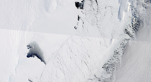 This image shows the Totten Glacier ice shelf in East Antarctica (the wrinkled white area at top left) on Sept. 25, 2013. Two large sea ice openings are visible, as are as several smaller ones. The open-water areas are bright black.