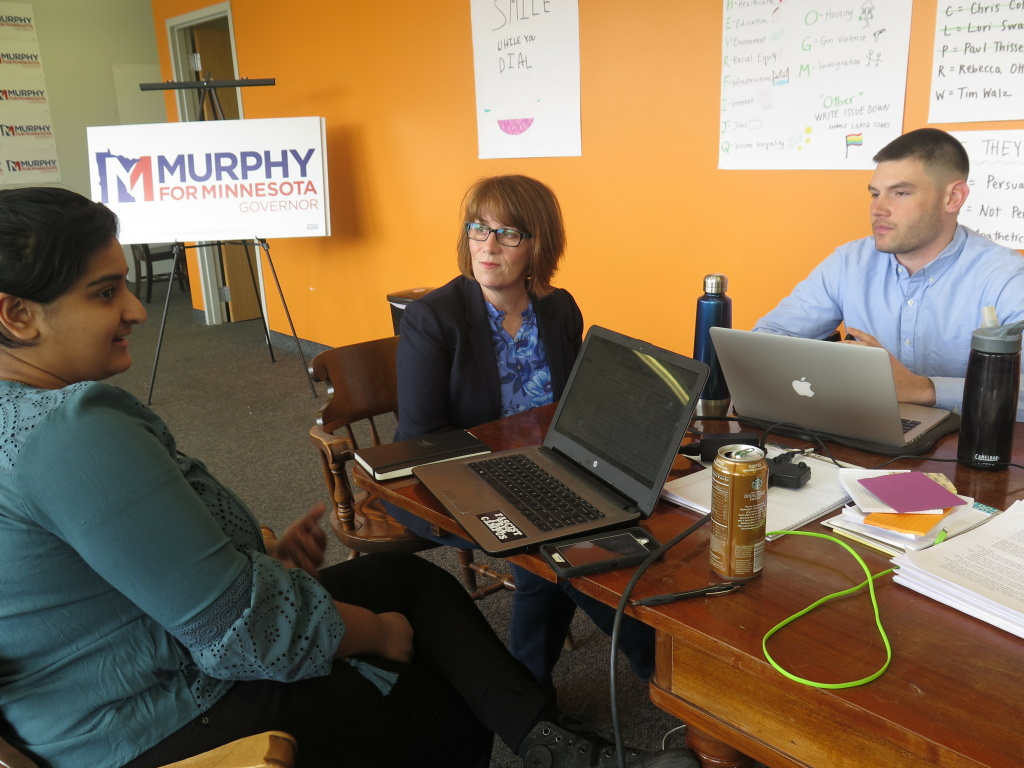 Campaign staff member Aisha Chughtai (left) speaks with Erin Murphy (center), a Democratic candidate for Minnesota governor, at the campaign's St. Paul headquarters as colleague Charles Cox looks on. Chughtai and Cox are members of a newly formed campaign workers union.