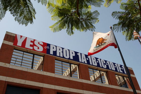 A California state flag flies near a pro-initiatives banner at the headquarters of the International Union of Operating Engineers Local 12