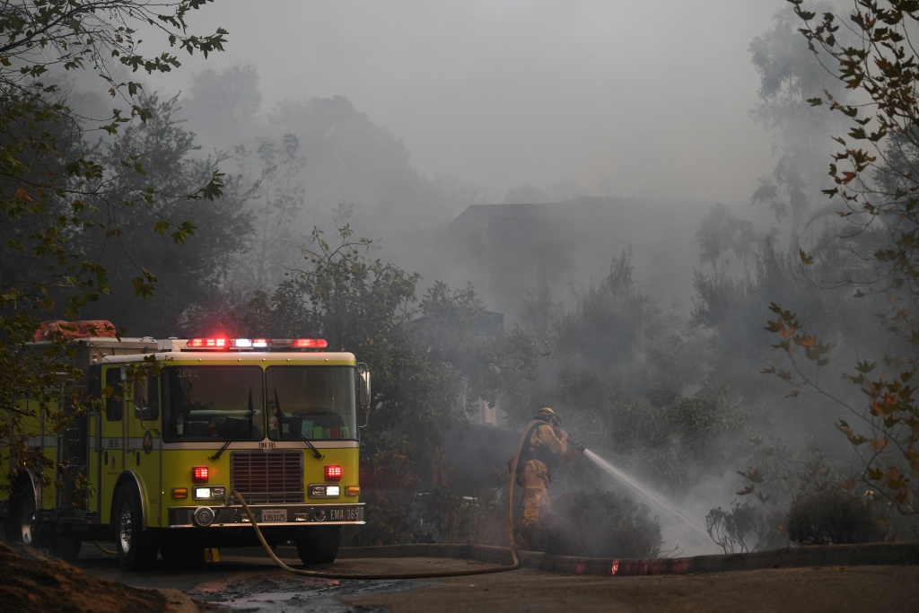 A firefighter douses flames from the Thomas Fire around a house that was saved as winds picked up and pushed the fire west on December 16, 2017 at in Montecito, California.