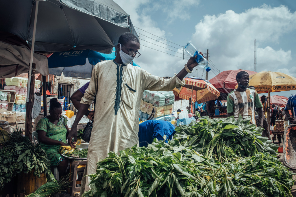 A vendor waters fresh greens for sale at a stall in a market in Abuja, Nigeria.