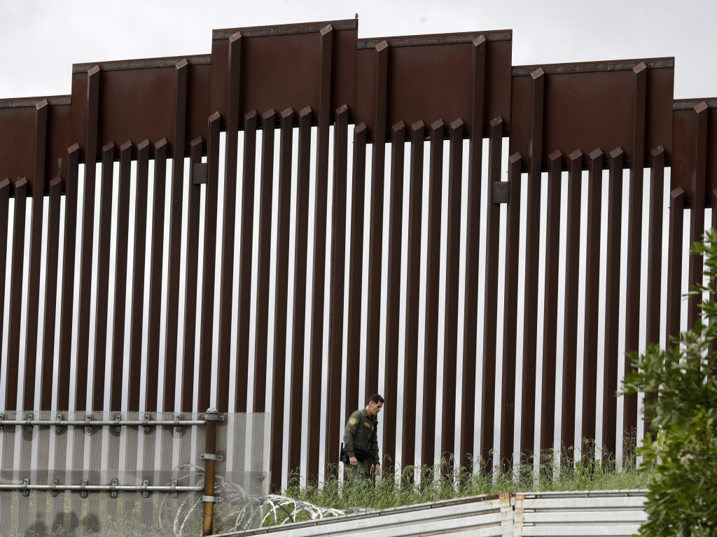 A Border Patrol agent walks along a border wall separating Tijuana, Mexico, from San Diego, in March 2020.