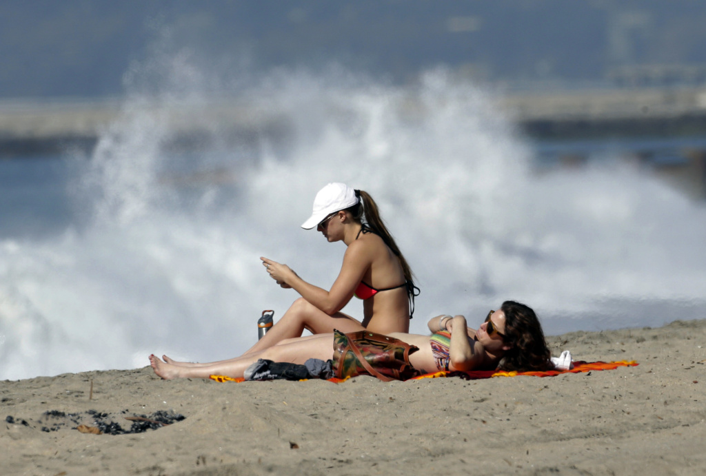 Olivia Brown, left, and her friend Elizabeth Foster take the sun at Playa Del Rey beach in Los Angeles Friday, Feb. 12, 2016. A February of dry skies and up to 95-degree heat is starting to dry up new fallen rain and snow, and raises worries this El Nino may not be the drought-buster California needs. Forecasters say a least some rain is on the way.(AP Photo/Nick Ut)