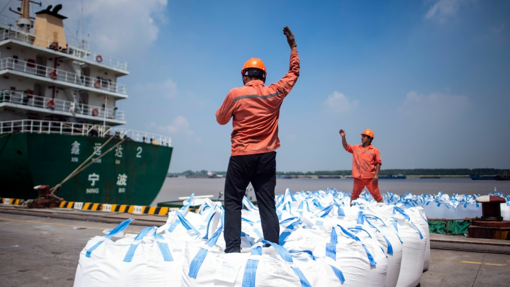 Dock workers unload bags of chemicals earlier this month at a port in Zhangjiagang, north of Shanghai.