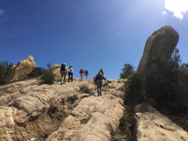 Hikers make their way along sandstone rock formations east of Corral Canyon Road.
