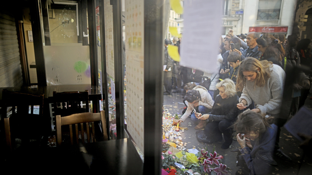 People place tributes and flowers outside La Belle Equipe restaurant on Rue de Charonne following Fridays terrorist attack.