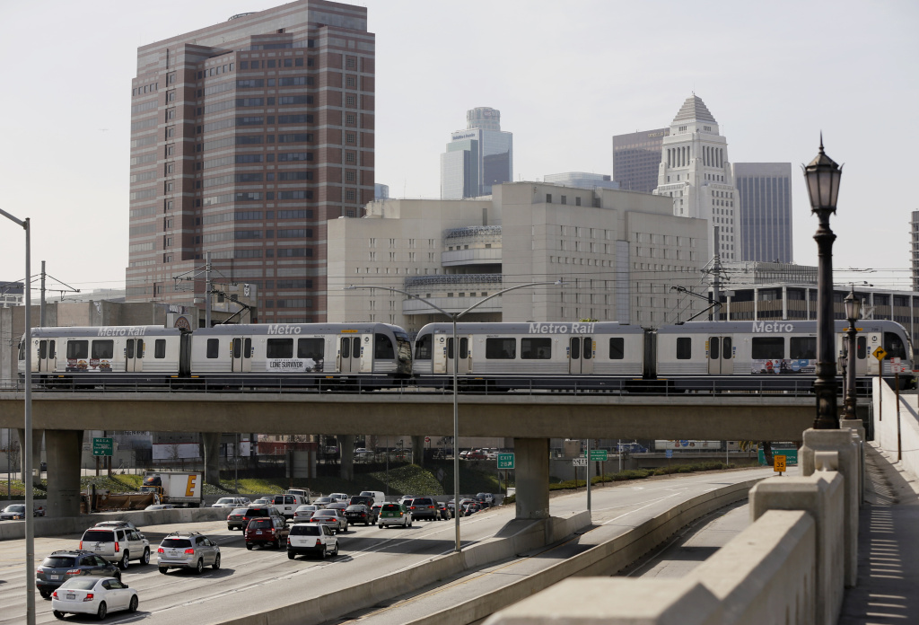A Metro Rail light train on the Gold Line travels over the 101 Santa Ana Freeway near Union Station in Los Angeles Thursday, Feb. 20, 2014. (AP Photo/Damian Dovarganes)