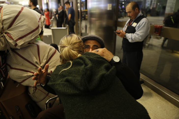 Abdalla Ahmed, facing camera, of Yemen, hugs attorney Julie Goldberg who accompanied him and his family from Djibouti after they arrived at Los Angeles International Airport Wednesday, Feb. 8, 2017, in Los Angeles. More than two dozen Yemenis who were stranded in Africa by President Donald Trump's travel ban have arrived into Los Angeles Wednesday. (AP Photo/Jae C. Hong)
