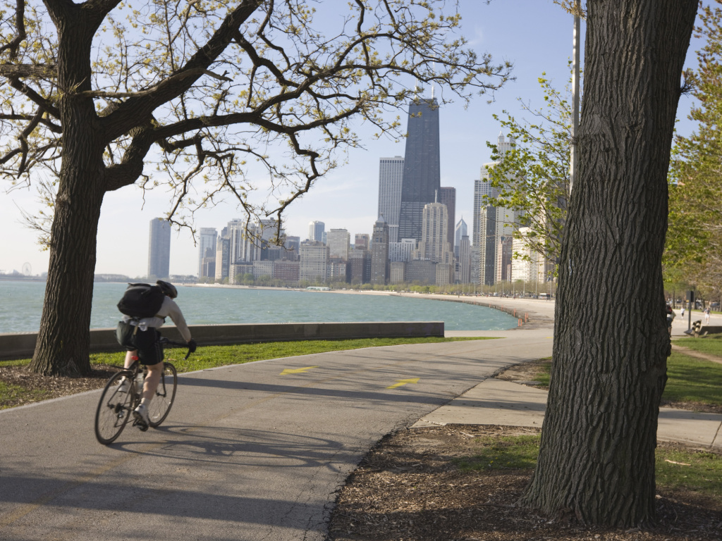 Cyclist by Lake Michigan shore, Gold Coast district, Chicago. Biking to work is associated with higher levels of well-being.