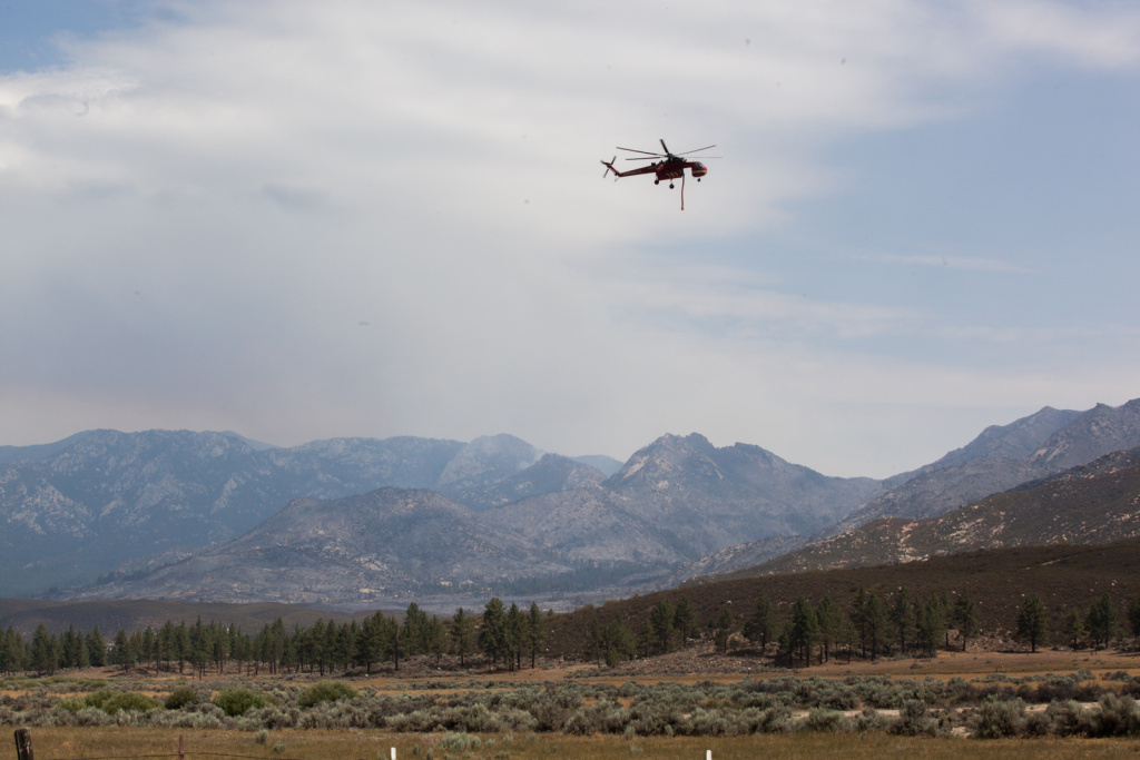A helicopter carrying water flies in front of mountains that were affected by the Mountain Fire.