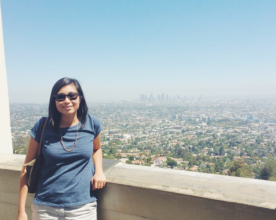 KPCC listener Melissa Afable poses in front of the downtown LA skyline from the Griffith Observatory.