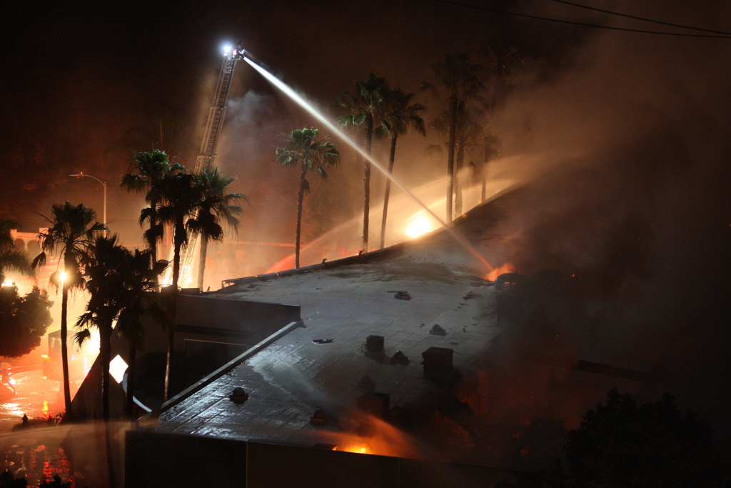 Firefighters spray water on a burning commercial structure at the Poinsettia fire, one of nine wildfires fueled by wind and record temperatures that erupted in San Diego County throughout the day, on May 14, 2014 in Carlsbad.