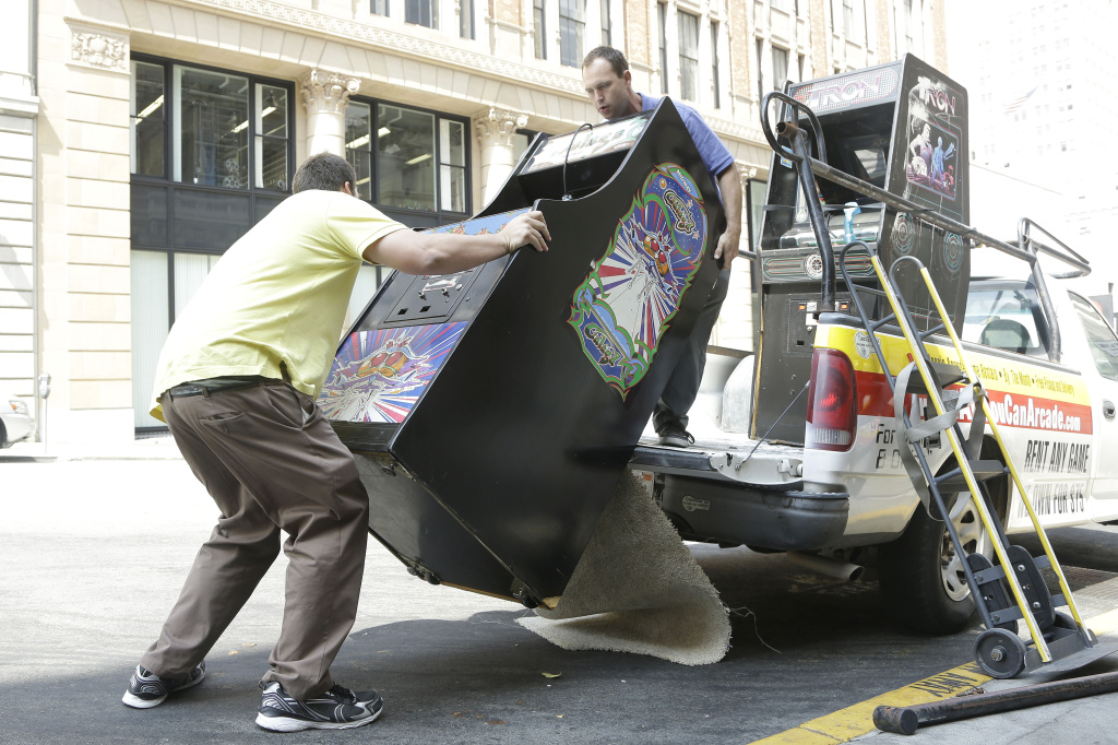 Timothy Peterson, left, and his brother Seth, co-owners of All You Can Arcade, unload a Galaga arcade game from their truck as they deliver it to the Eleven Inc office in San Francisco, Tuesday, July 30, 2013. A new startup company run by two San Francisco Bay area brothers will deliver any of a suite of retro 1980s classic video games and let you keep them in your home or office for $75 per month.
