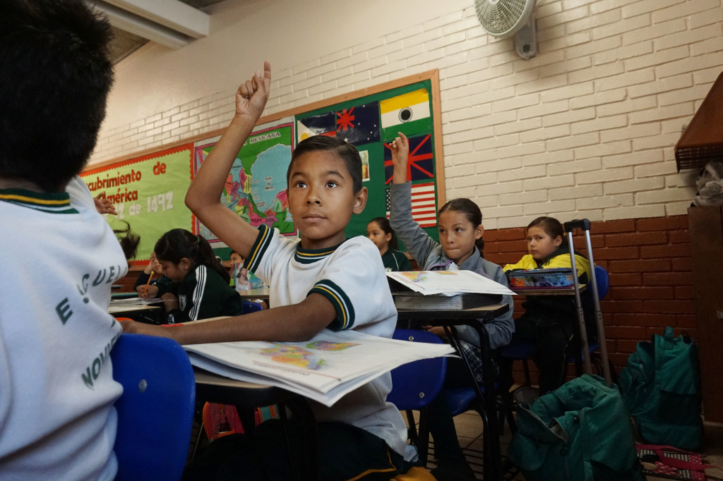Anthony David Martinez raises his hand in class at the Escuela 20 Noviembre school in Tijuana, Mexico.