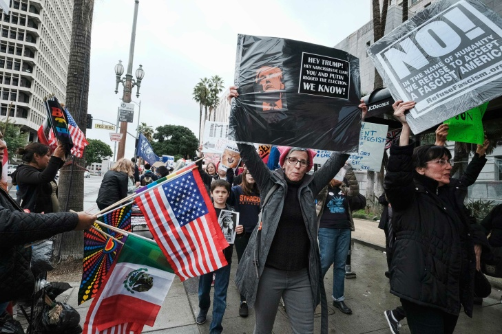 Protesters march down a street past Los Angeles City Hall on Monday, Feb. 20, 2017. Demonstrators gathered to express their opposition to President Donald Trump and take part in a