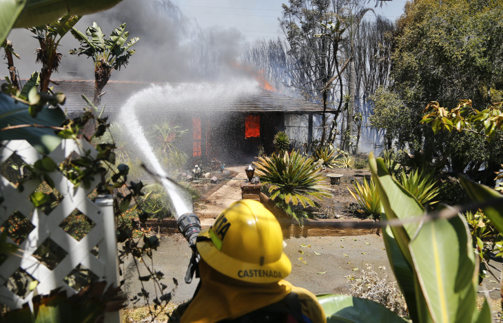 A firefighter pours water onto a fully engulfed home Wednesday, May 14, 2014, in Carlsbad, Calif. A brush fire Wednesday forced evacuation of thousands of people in the city of Carlsbad where at least two homes burned amid a Southern California heat wave that sparked several blazes.